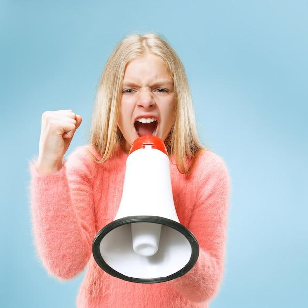 Tiener meisje aankondiging met megafoon op blauwe studio Gratis Foto