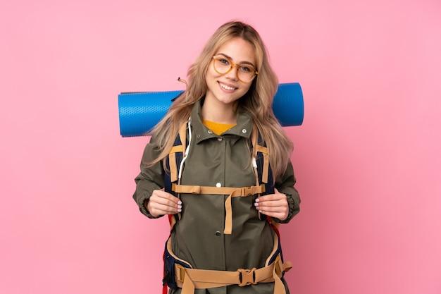 Tiener russisch bergbeklimmer meisje met een grote rugzak geïsoleerd op roze muur met bril en lachend Premium Foto