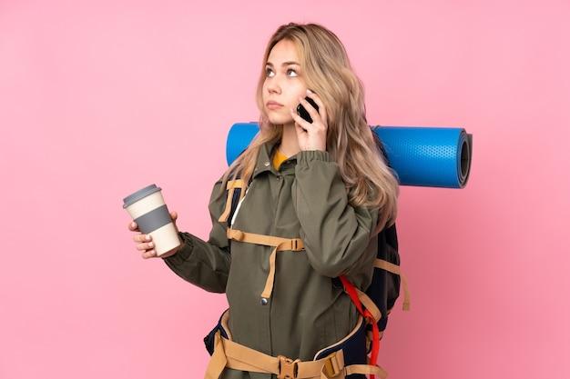 Tiener russisch bergbeklimmer meisje met een grote rugzak geïsoleerd op roze muur met koffie om mee te nemen en een mobiel Premium Foto