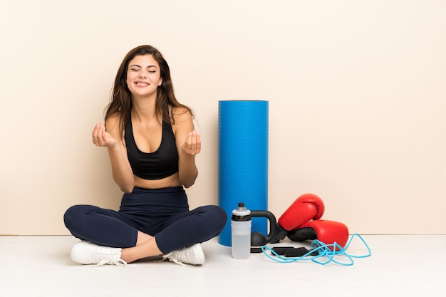Tiener sport meisje zittend op de vloer geld gebaar maken Premium Foto