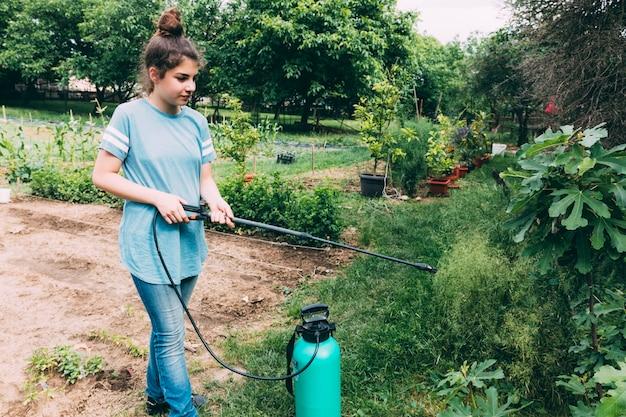 Tiener spuiten planten in de tuin Gratis Foto