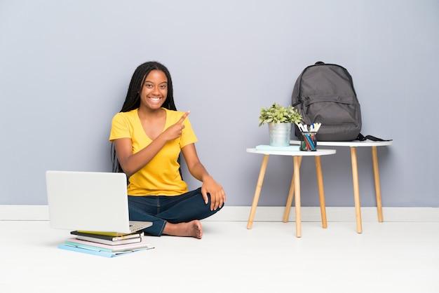 Tiener student meisje zittend op de vloer wijzende vinger naar de kant Premium Foto