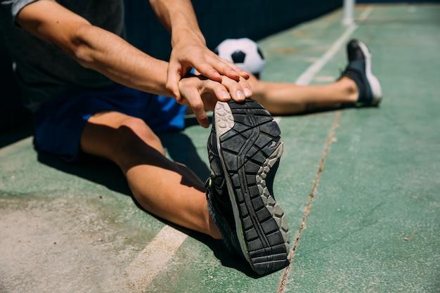 Tiener uitrekkende voet in voetbalveld Gratis Foto