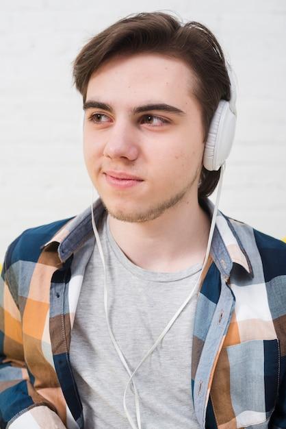 Tienerjongen die aan muziek luistert Gratis Foto
