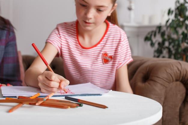 Tienermeisje bij ontvangst bij de psychotherapeut. psychotherapie sessie voor kinderen. de psycholoog werkt met de patiënt. het meisje tekent potlood met potlood op papier samen met een arts Premium Foto
