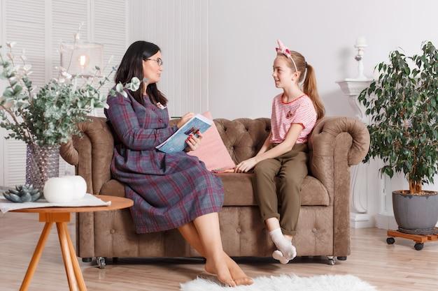 Tienermeisje bij ontvangst bij de psychotherapeut. psychotherapie sessie voor kinderen. de psycholoog werkt met de patiënt. meisje lachend zittend op een bank naast een zittende vrouwelijke arts therapeut Premium Foto