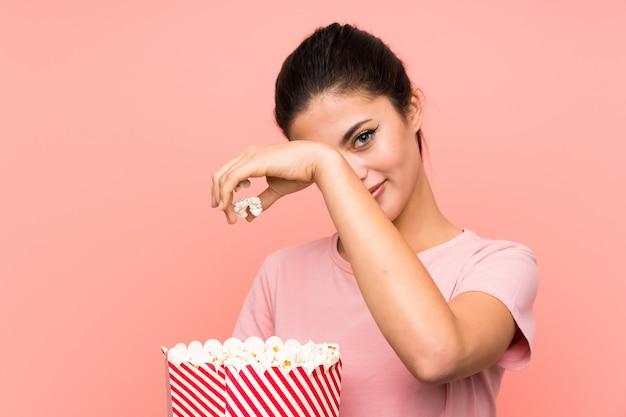 Tienermeisje die over geïsoleerde roze muur popcorns eten Premium Foto