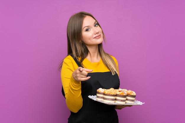 Tienermeisje die veel verschillende minicakes over geïsoleerde purpere achtergrondpuntenvinger houden op u Premium Foto