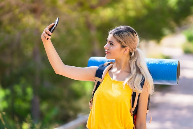 Tienermeisje die wandelen bij in openlucht het maken van een selfie Premium Foto