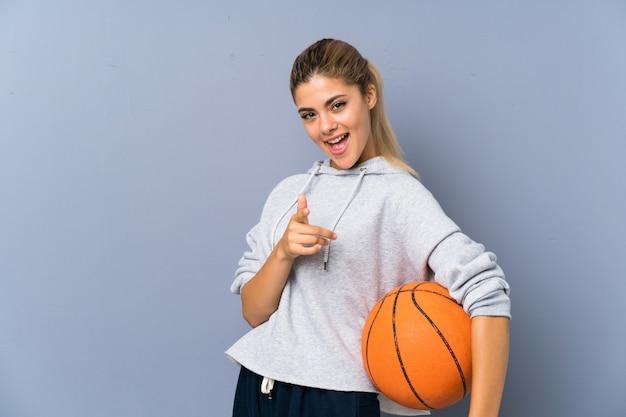 Tienermeisje het spelen basketbal richt vinger op u met een zekere uitdrukking Premium Foto