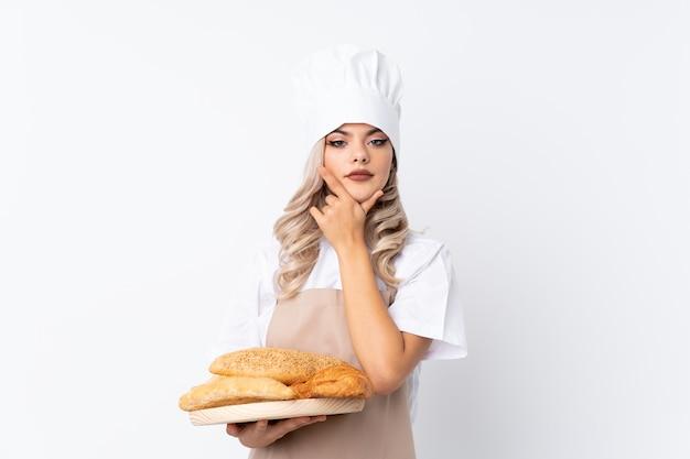Tienermeisje in eenvormige chef-kok. vrouwelijke bakker die een lijst met verscheidene broden over geïsoleerd wit houden die een idee denken Premium Foto
