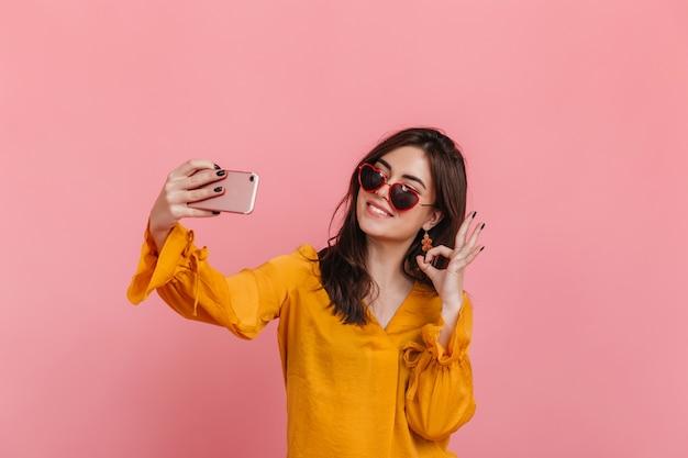 Tienermeisje in lichte blouse en ongebruikelijke zonnebril vertoont teken