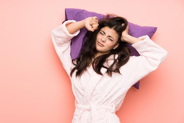 Tienermeisje in peignoir over roze backgrounnd en geeuw Premium Foto