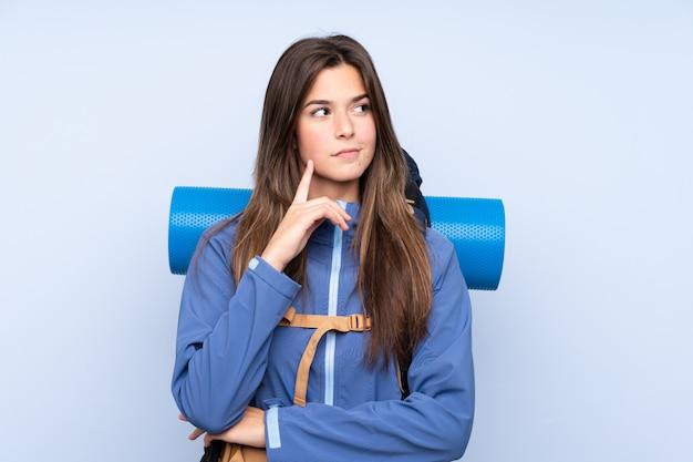 Tienermeisje met een bergbeklimmingsrugzak over blauwe muur Premium Foto