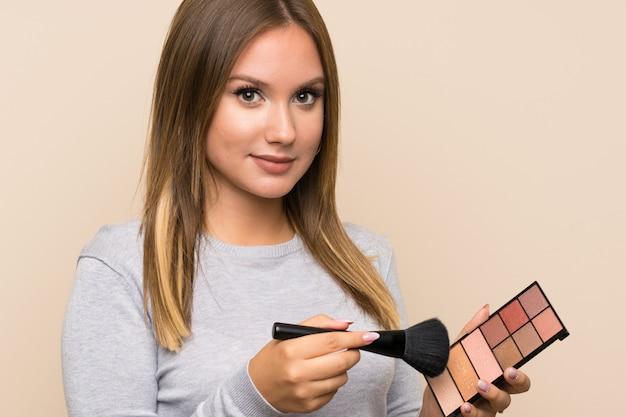 Tienermeisje met make-uppalet over geïsoleerde muur Premium Foto