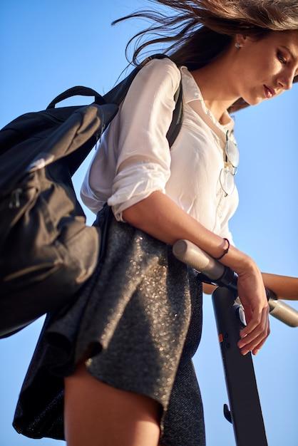 Tienermeisje met rugzak, rok en shirt rijden op de elektrische scooter Premium Foto