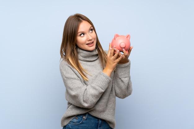 Tienermeisje met sweater over geïsoleerde blauwe achtergrond die een grote spaarpot houden Premium Foto