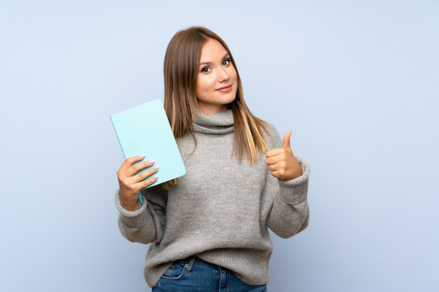 Tienermeisje met sweater over geïsoleerde blauwe achtergrond die en een boek houden lezen Premium Foto