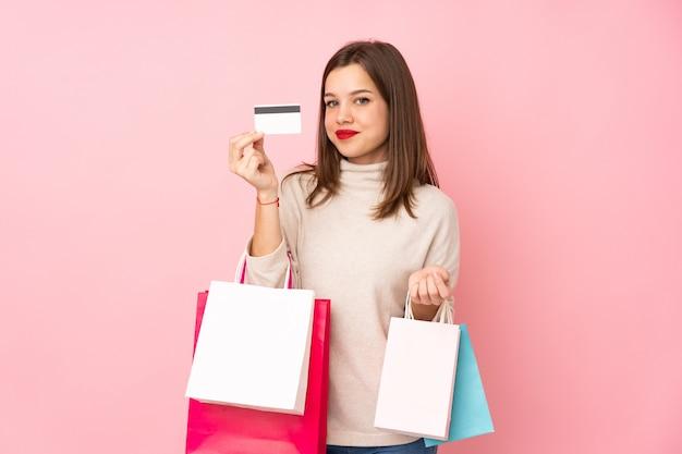 Tienermeisje op roze het winkelen van de muurholding zakken en een creditcard wordt geïsoleerd die Premium Foto