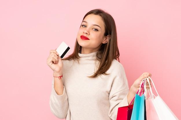 Tienermeisje op roze muurholding het winkelen zakken en een creditcard Premium Foto