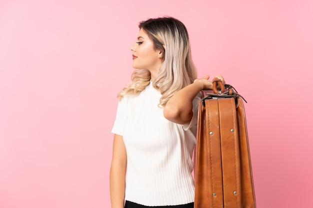 Tienermeisje over geïsoleerde roze achtergrond die een uitstekende aktentas houden Premium Foto