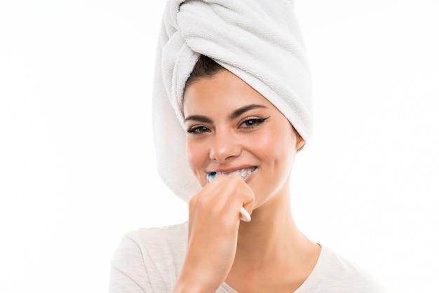 Tienermeisje over geïsoleerde witte muur die haar teeths borstelt Premium Foto