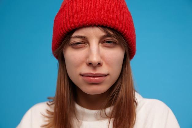 Tienermeisje, verdacht uitziende vrouw met donkerbruin haar. het dragen van een witte trui en een rode hoed. mensen en emotioneel concept. close-up, geïsoleerd over blauwe muur Gratis Foto