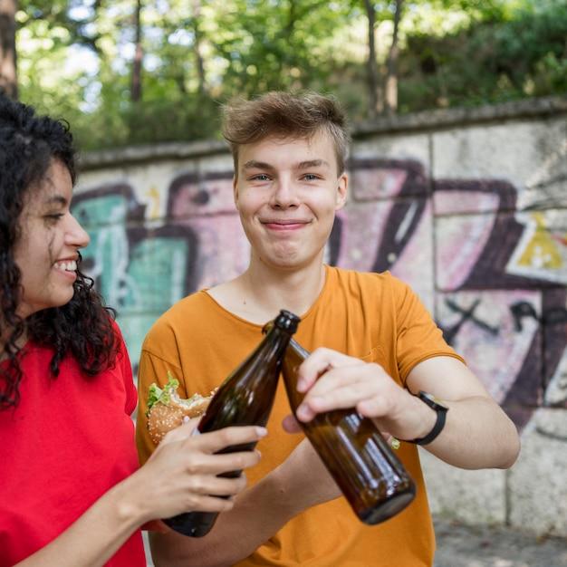 Tieners juichen met flessen en hamburger buiten eten Gratis Foto