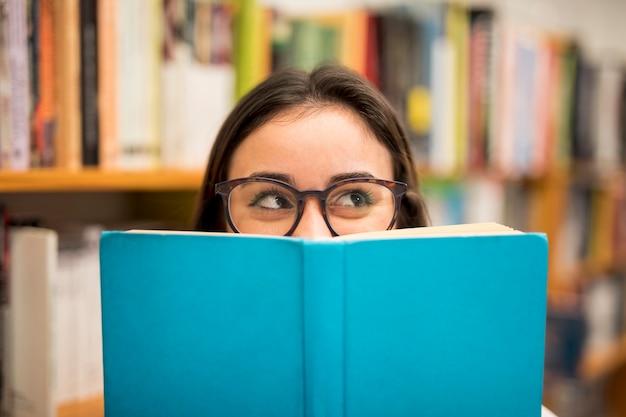 Tienerschoolmeisje die uit boek gluren Premium Foto