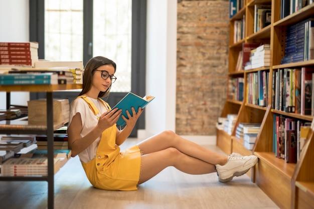 Tienerschoolmeisje met boek op vloer Gratis Foto