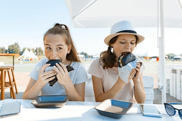 Tienersmeisjes met eetlust eten zwarte fastfoodburger Premium Foto