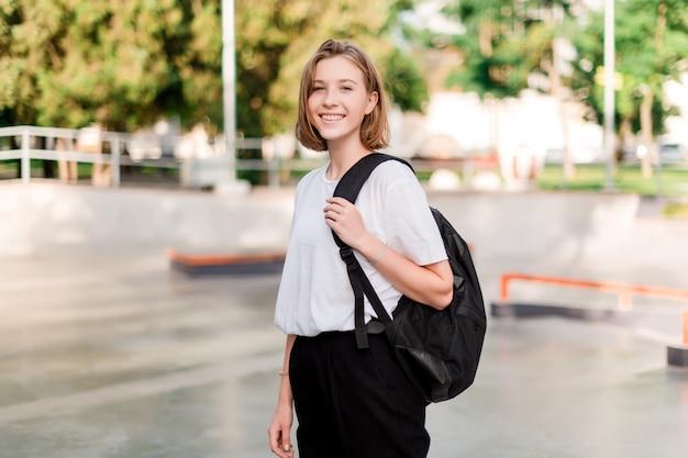 Tienerstudentenmeisje met een schooltas in een park Premium Foto