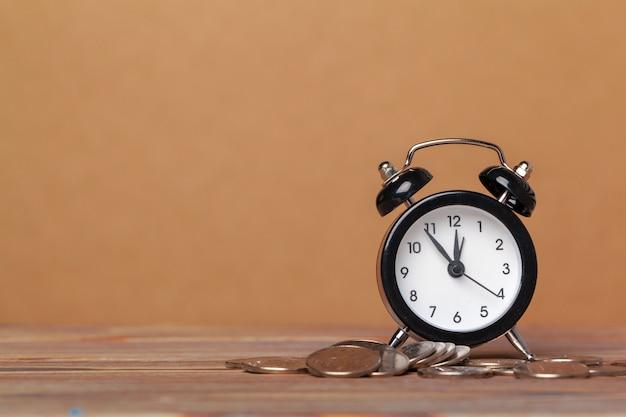 Tijd is geld, tafelklok met munten Premium Foto