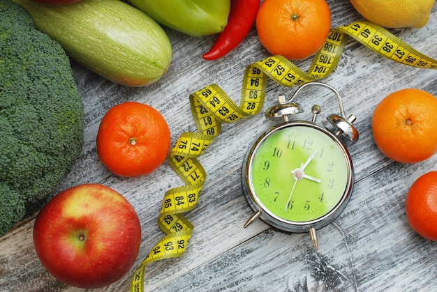 Tijd om af te vallen. fruit, groenten en wekker. dieet. Premium Foto