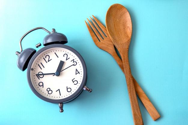 Tijd om gewicht te verliezen, controle of tijd aan dieetconcept, wekker met een gezonde decoratie van het hulpmiddelconcept op blauwe achtergrond te eten Premium Foto