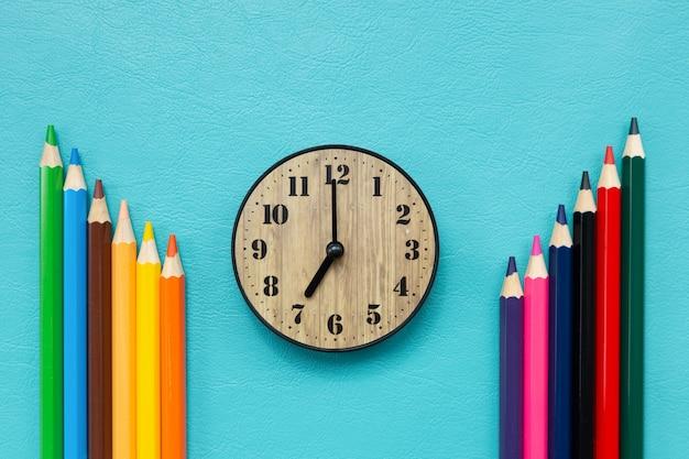 Tijd terug naar school met klok en kleurpotloden Gratis Foto