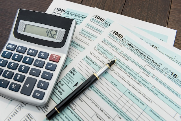 Tijd voor federale belastingformulier met pen en rekenmachine bureau papierwerk Premium Foto