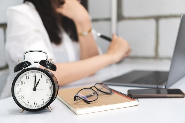 Tijdbeheer, zwarte wekker met vage bedrijfsvrouw werkt met laptop. Premium Foto