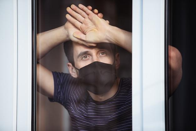Tijdens de quarantaine blijft een man geïsoleerd thuis. coronapandemie. de man kijkt uit het raam de straat in Premium Foto