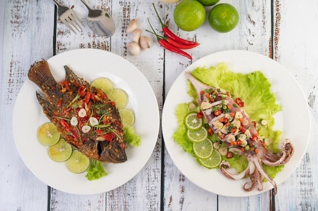 Tilapia gebakken met chili saus en inktvis, citroen en knoflook op een plaat op een witte houten tafel. Gratis Foto