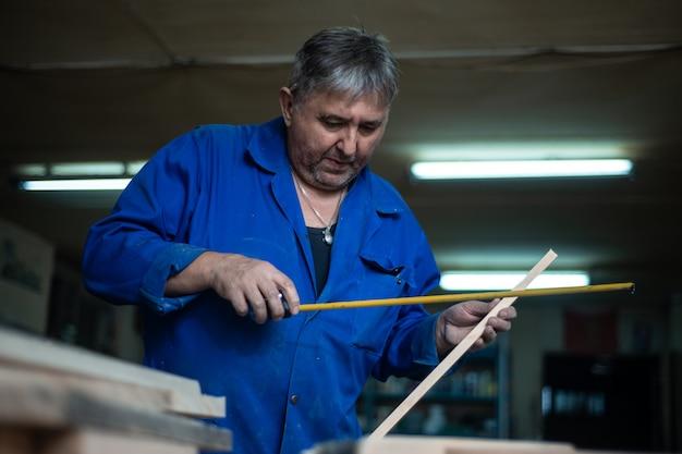 Timmerman aan het werk in de werkplaats, een man doet metingen Premium Foto