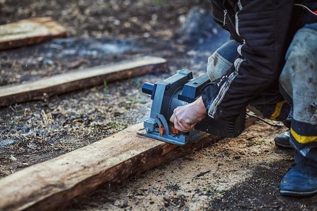 Timmerman die cirkelzaag voor hout gebruikt. detailopname Premium Foto