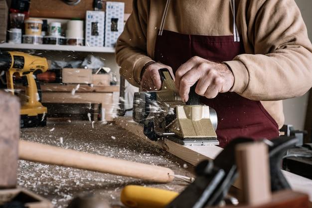 Timmerman die het hout met een elektrische borstel werkt Premium Foto
