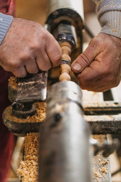 Timmerman die hout gebruikt om sculpturen te maken in het atelier Gratis Foto