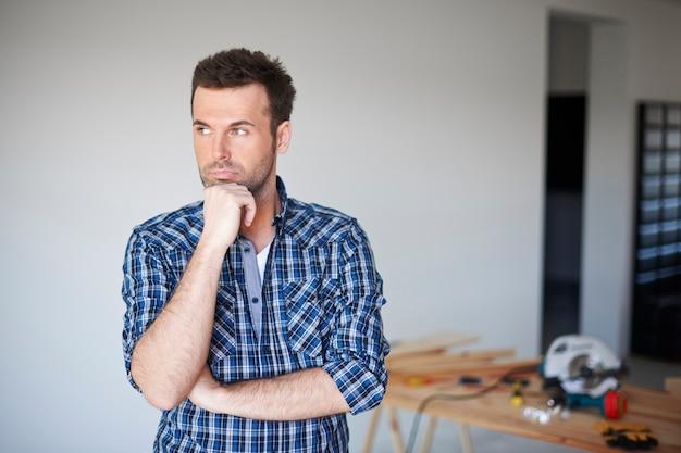 Timmerman die in een huis werkt en denkt Gratis Foto