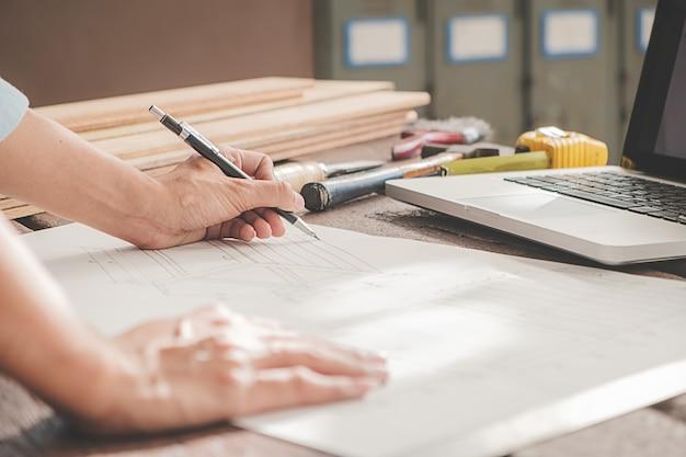 Timmerman die met apparatuur aan houten lijst in timmerwerkwinkel werken. vrouw werkt in een timmerwinkel. Premium Foto