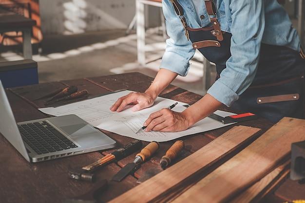 Timmerman die met apparatuur aan houten lijst in timmerwerkwinkel werken. Premium Foto