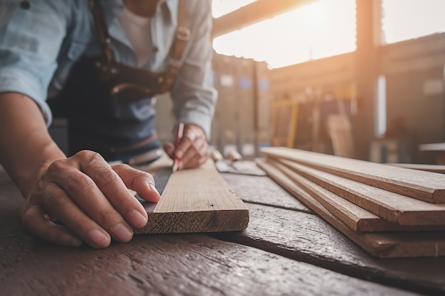 Timmerman die met materiaal aan houten lijst in timmerwerkwinkel werken. Premium Foto