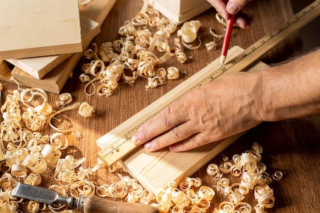 Timmerman die met potlood aan een stuk hout werkt Gratis Foto