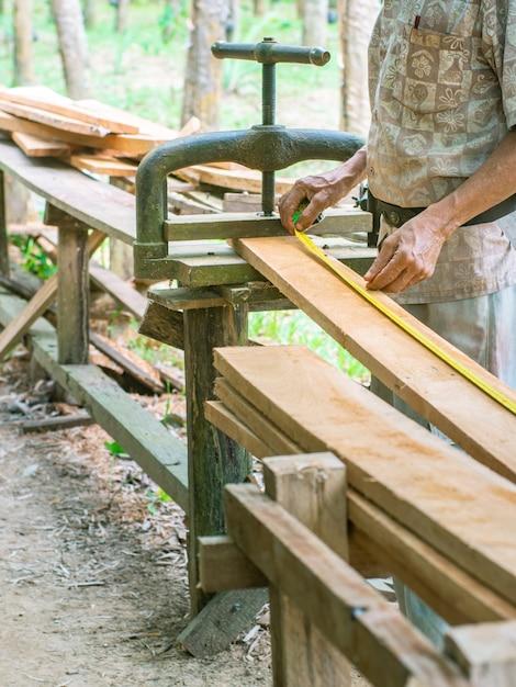 Timmerman meet de lengte van de plank geklemd met vintage metalen comprimeergereedschap. Premium Foto